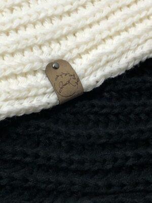 Étiquette pliable en Xtrasuede de couleur XS-4 avec rivet noir apposé sur tricot