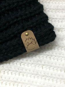 Étiquette pliable en Xtrasuede de couleur XS-5 avec rivet bronze apposé sur tricot